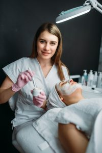 Female doctor holds cream and brush in hands